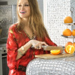 Blonde in modern kitchen cuts oranges — Stock Photo