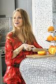 Blonde in modern kitchen cuts oranges — Stock Photo