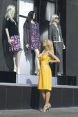 Blonde looks on the show-window — Stock Photo