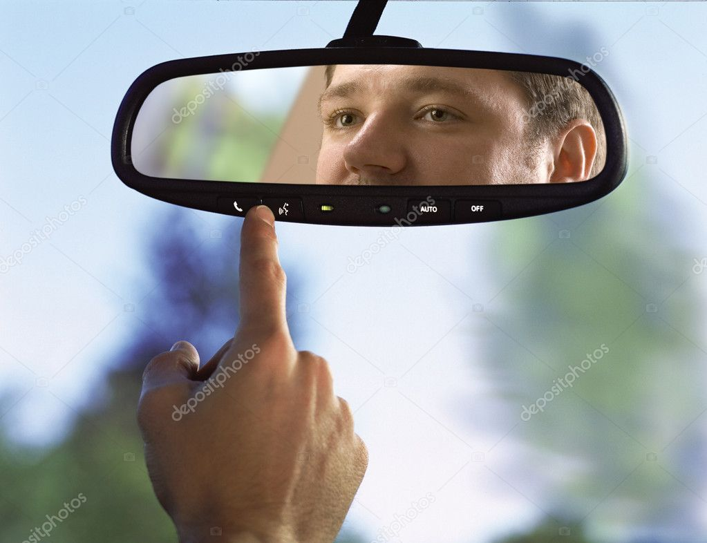 Man sits on driver's seat and Looks in the rear-view mirror — Stock Photo #2686607