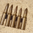 Stock Photo: Ammunition on sand