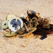 Stock Photo: Parts of clockwork mechanism on the sand