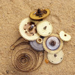 Parts of clockwork mechanism on the sand — Stock Photo #2550652