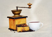 Coffee mill and cup of hot black coffee — Stock Photo