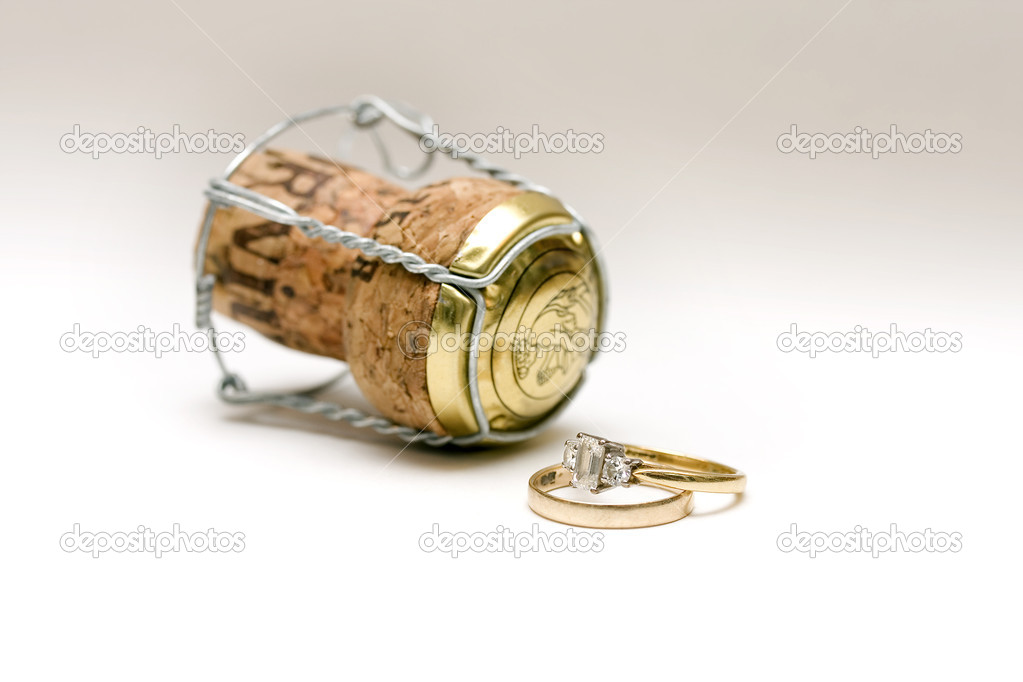 A wedding and engagement ring with a champagne cork on white background — Stock Photo #2264728