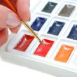 Hand choosing colour with brush — Stock Photo #2407321