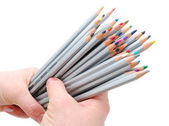 Two hands holding colored pencils — Stock Photo