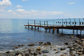 Old rusty pier in the water — Stock Photo