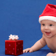 Baby in santa's cap with gift — Stock Photo