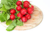 Bunch of radishes on wooden board — Stock Photo
