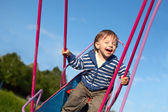 Laughing baby on the swing — Stock Photo