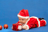 Baby in santa's suit with gift — Stok fotoğraf