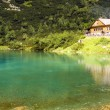 Stock Photo: Chalet next to a green mountain lake