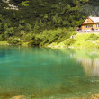 Chalet  next to a  green mountain lake - Stock Photo