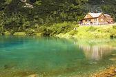 Chalet next to a green mountain lake — Stock Photo