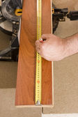 Carpenter measuring wood floor — Stock Photo