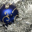 Blue christmas ball on silver tinsel — 图库照片