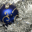 Blue christmas ball on silver tinsel — Stock fotografie