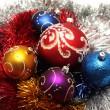 Christmas balls on tinsel background — Stock Photo