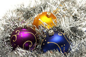 Christmas balls on silver tinsel — Stockfoto