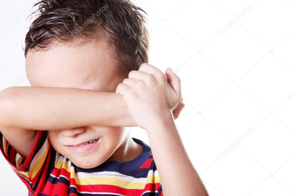 Child crying covering his face with his hand.   Stock Photo #2447276