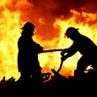 Foto Stock: Two fire fighters and flames
