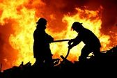 Two fire fighters and flames — Stockfoto