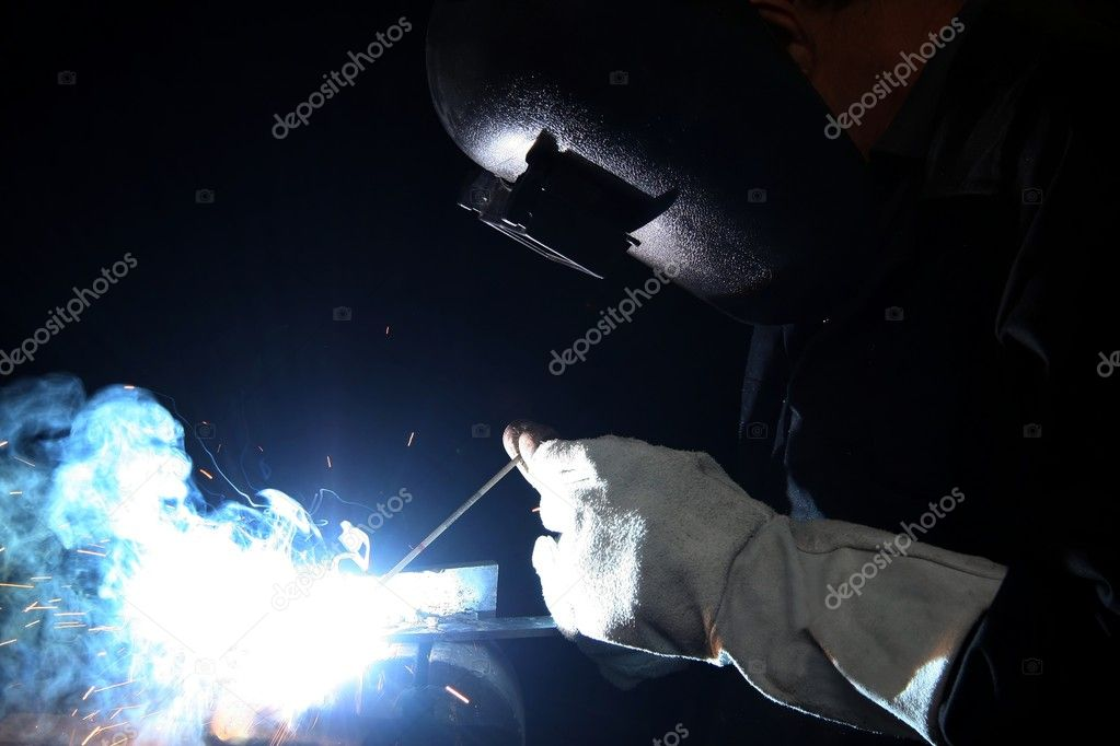 Welder with protective gloves and helmet welding steel  Stock Photo #2320959