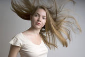Young girl with flying fair hair — Stock Photo