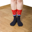 Legs in socks on a wooden floor — Stock Photo