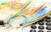 Euro with calculator and magnifier — Stock Photo