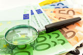 Euro Notes with calculator and magnifier — Stock Photo