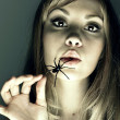 Young woman with spider in a mouth — Stockfoto