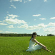 Beautiful young woman on a green field — Стоковая фотография