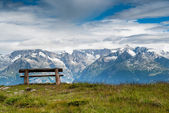 Empty park bench in high mountains — Stock Photo