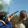 Man shooting clay pigeons being instruct - Foto de Stock