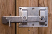 Metal latch on a wooden barn door — Stock Photo