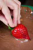 Hand dipping strawberry in chocolate — Stock Photo