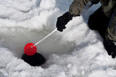 Cleaning out a hole for ice fishing — Stock Photo