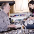 Old man and girl washing dishes - Stock Photo