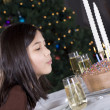 Little girl blowing  birthday cake - Stock Photo