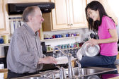 Old man and girl washing dishes — Stock Photo