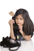 Girl talking on rotary phone, worried — Stock Photo