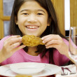 Girl eating fried chicken drumstick — Stock Photo