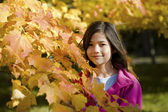 Girl standing amongst autumn leaves — Stock Photo