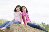 Two girls on haystack — Stock Photo