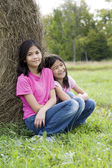 Two girls by haystack — Stock Photo