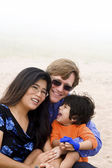 Multiracial family sitting on beach — Stock Photo
