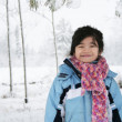 Little girl under snow covered trees — Stock Photo