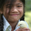 Little girl holding pet chick — Stock Photo